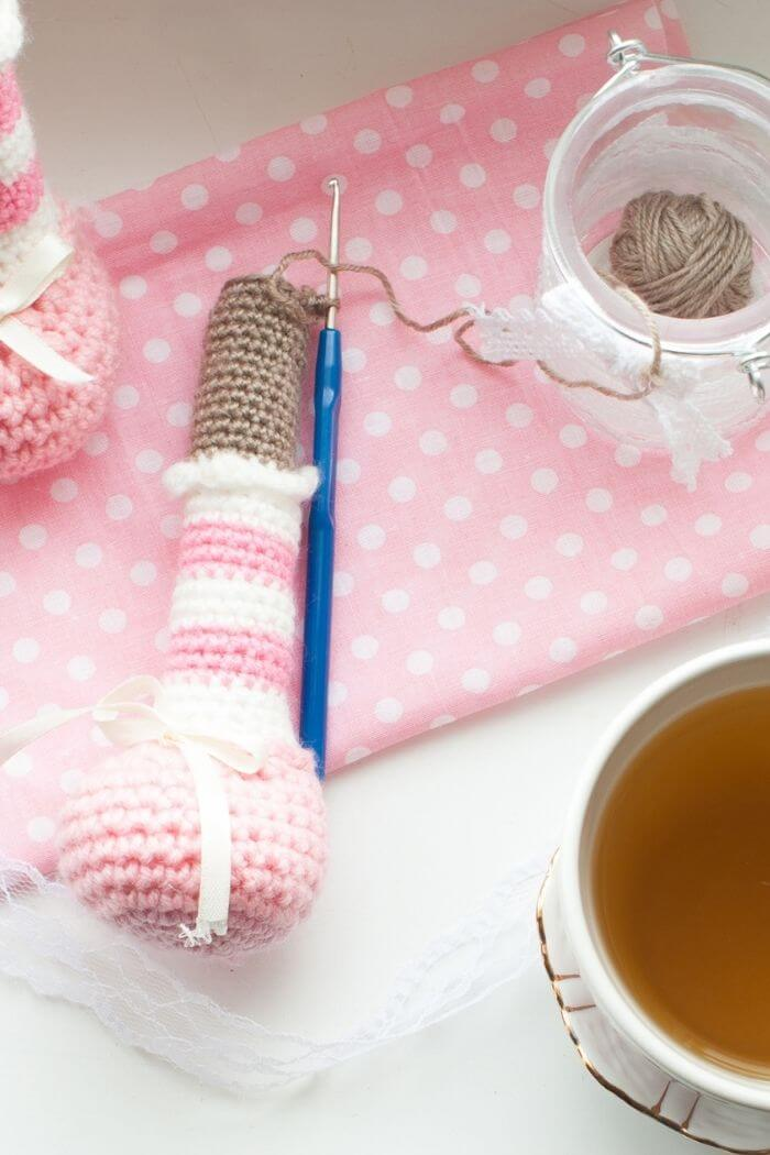 a person crocheting a toy and having a cup of tea